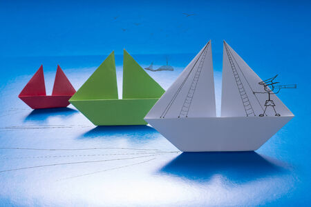 Drawn captain looking through spyglass on Paper Boat Sailing with other on Blue paper sea with Drawn Details  Origami Ship photo