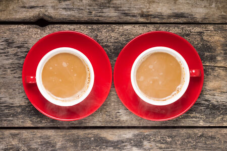 Two Red Cups of Coffee with Milk on old Wood Background  Top View
