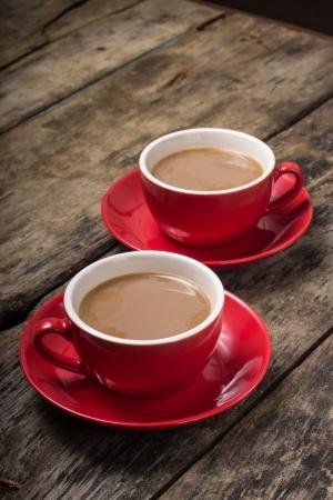 Zwei rote Tassen Kaffee mit Milch auf alten Holz-Hintergrund