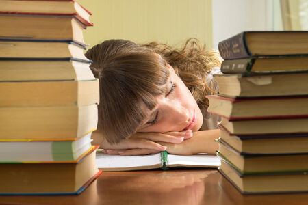 Young girl studying with books. Female Student sleeping during learning photo