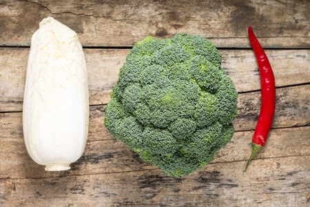 chinesse: Broccoli, Chinesse Cabbage and Red Chilli Pepper on grunge wooden board. Top View Stock Photo