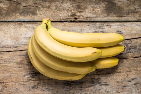 Bunch of Bananas on Grunge Wooden Background. Top View 스톡 콘텐츠
