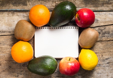 Blank Recipe Notepad with Different Fruits Around on Wood Background photo
