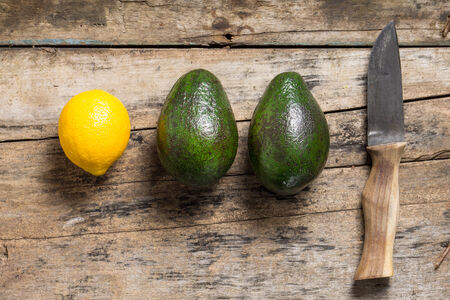 Avocado and Lemon with Knife on Old wooden Board photo