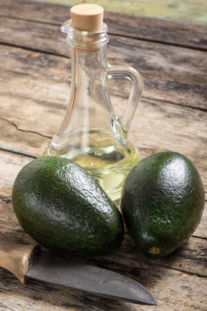 Two avocado with Knife and Bottle of Oil on Wood Background