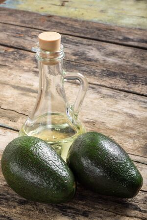 Two Raw Avocado with Bottle of Oil on Grunge Wood Background