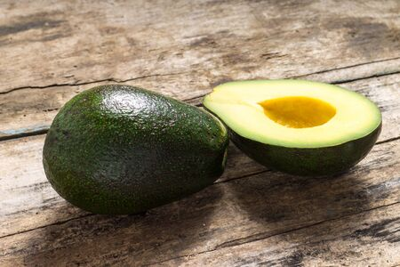 Whole and cut in half Avocado on wood background Stock Photo