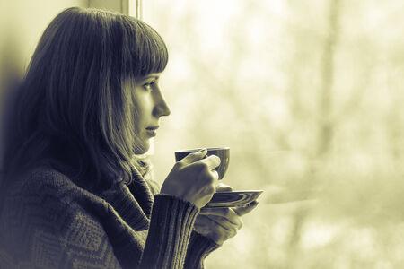 Beautiful girl drinking coffee or tea near window. Toned Image photo