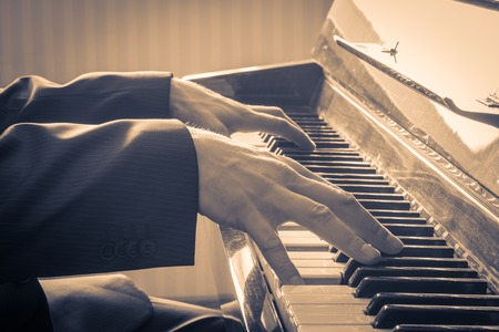 피아노를 연주하는 남자의 손. 복고 스타일입니다. 따뜻한 톤 컬러