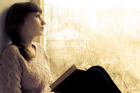 Young woman reading book near the window. Warm toned image 스톡 콘텐츠
