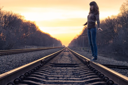 rail travel: Young adult girl balance on railroad in sunset beams