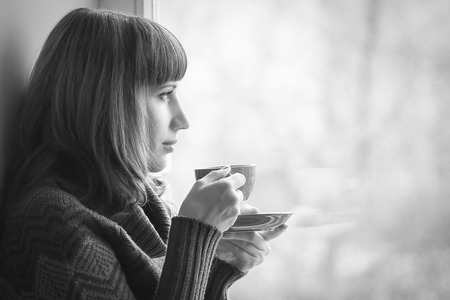 Beautiful girl dreaming with cup of coffee or tea near window. Black and  White Image photo