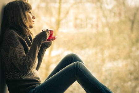 Beautiful girl dreaming with cup of coffee or tea near window Stock Photo
