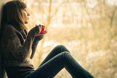 Mooi meisje droomt met een kopje koffie of thee in de buurt raam