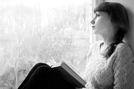 Young adult girl reading book near the window  Black and White image photo