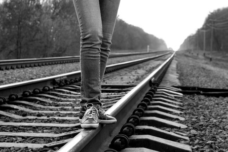 b w: Girl walking across railroad   B W image Stock Photo