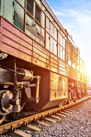 Old train on railway with sun on sky