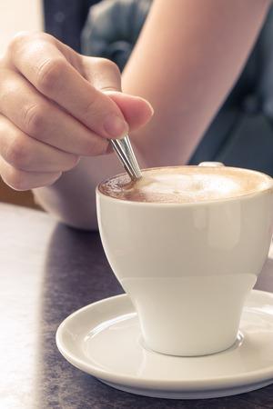 Koffie in de ochtend. Kopje cappuccino in Cafe. Meisje proeverij crème
