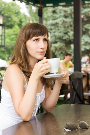 Portrait of young woman sitting in cafe. Dreaming girl with cup of coffee photo