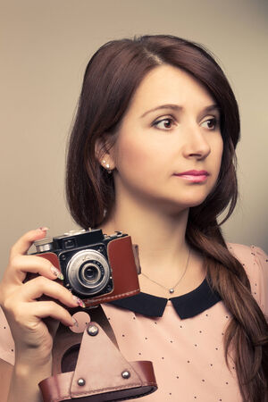 Young hipster woman make a photography with old camera. Warm color toned image. photo