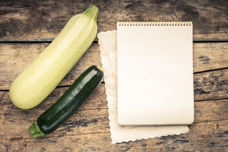Warm color toned series of Vegetables with recipe book on wooden table. Old wood background. Menu background. Squash photo