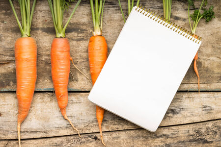 Menu background. Recipe book with fresh ripe carrots on wooden table. Top view. photo