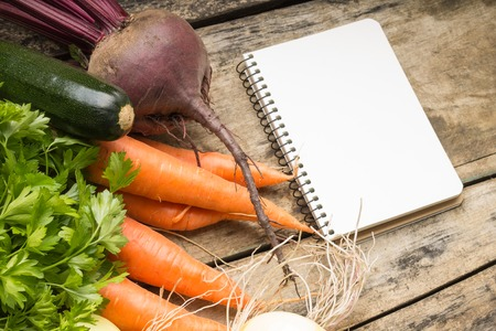 recipe background: Recipe background. Fresh vegetables with blank page of cookbook. Stock Photo
