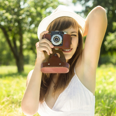 Young woman posing with old film camera in summer park. Girl in White hat photograph with manual camera Stock Photo - 30704449