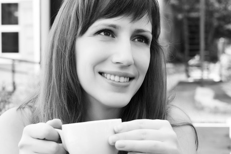 Portrait of young smiling woman in cafe. Black and white image of european girl with cup of coffee Stock Photo - 30704453