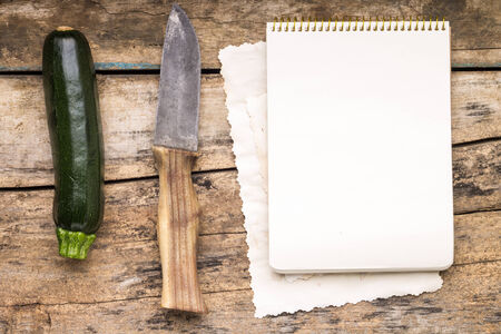 Series of Fresh Vegetables with knife at the wooden table. Squash with cookbook. Menu background photo