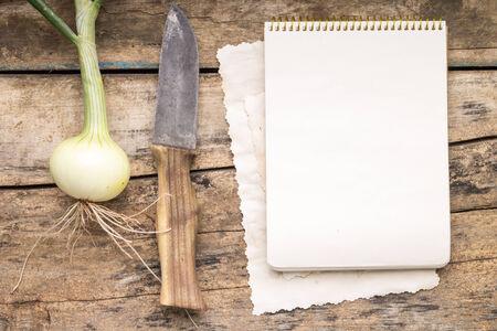 Reihe von frischem Gemüse mit Messer auf dem Holztisch. Zwiebel mit Kochbuch. Menü-Hintergrund Standard-Bild