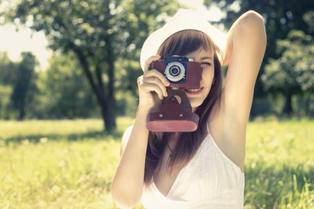 Beauty girl with old film camera in summer park. Toned image Stock Photo - 30704489