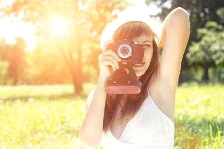 Beautiful hipster woman posing with old film camera in summer park with sunbeams. Stock Photo - 30704490
