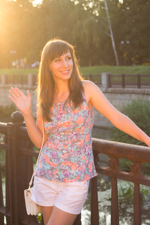 Young beautiful hipster woman greeting  somebody at the embankment Stock Photo - 30704492