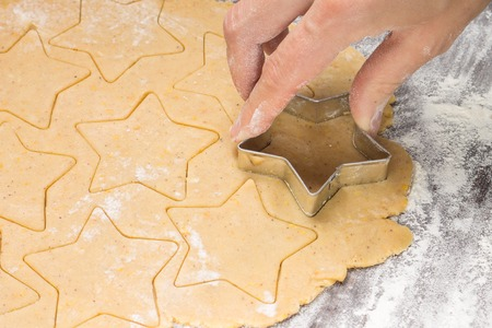 cut: Making gingerbread christmas cookies with metal cutter. Ginger dough and flour Stock Photo