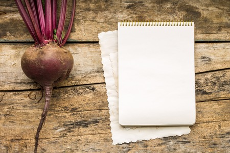 Menu background. Vegetables on table with cook book. Cooking with recipe book. Red beet photo