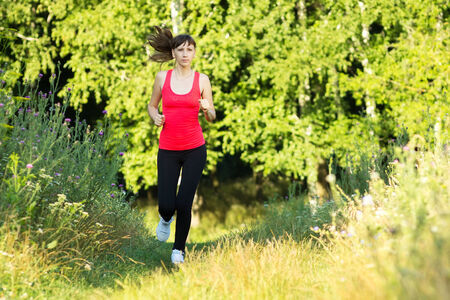 sportwear: Young woman dressed in sportwear jogging at summer park