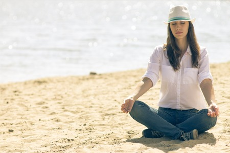 Young woman in white hat relax at the beach in summer midday. Hipster girl in meditation near the sea photo