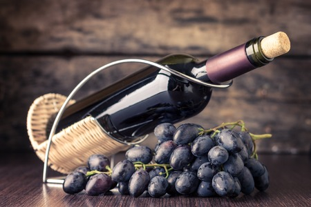 still life of wine: Winery background. Bottle of red wine in holder with cluster of dark blue grapes on wooden table. Toned image