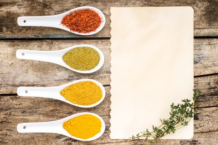 recipe background: Spices recipe background. Variety of condiments with recipe sheet on old wooden table. Top view Stock Photo