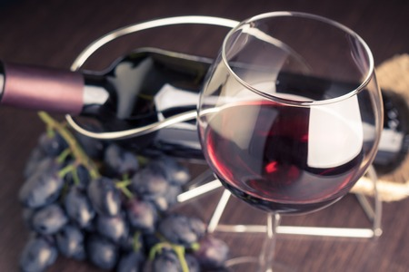 botella: Copa de vino tinto con la botella y las uvas. Imagen de fondo en tonos Bodega