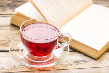 Literature background. Cup of hot tea with opened book on wooden table photo