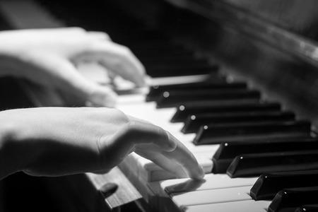 teclado de piano: Niña que juega en el teclado del piano. Imagen blanco y negro con enfoque selectivo Foto de archivo