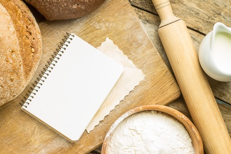 Menu background. Bakery ingredients with blank recipe book on wooden table photo