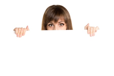 stared: Portrait of young beautiful woman behind white blank board. Stock Photo
