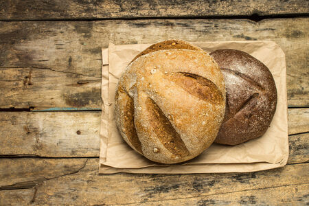 Loafs of different species of bread on wood background with paper bag. Top view photo