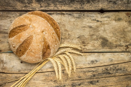 Loaf of bread with wheat ears on wood background photo
