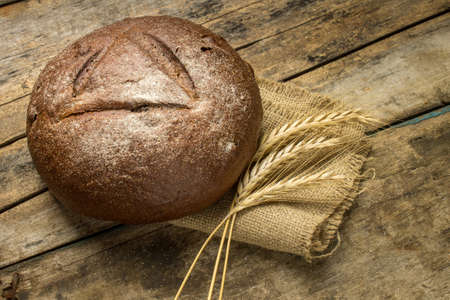 lithuanian: Loaf of rye bread with wheat ears on wood background Stock Photo