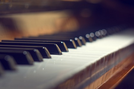 selective focus: Piano keyboard background with selective focus. Warm color toned image