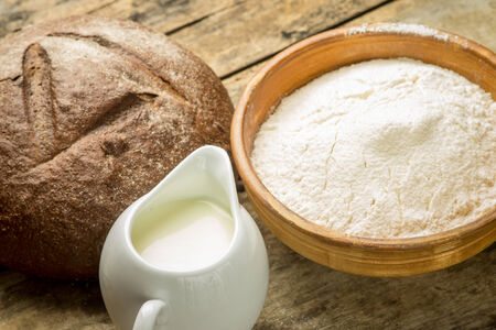 Bakery ingredients background. Rye bread with flour and milk on wooden table photo